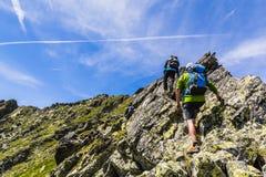 岩石土坎的三个登山人 库存图片