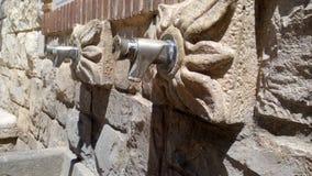 岩石在墙壁上的水龙头 库存照片