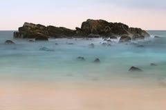 岩石在展望期的海洋在日落以后 库存图片