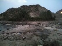 岩石在山附近被包裹的土地和棕榈 免版税库存图片