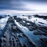 岩石在日落的海 托斯卡纳海岸意大利 免版税图库摄影