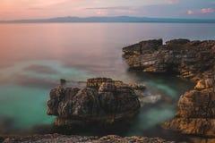 岩石在日落的海 库存照片