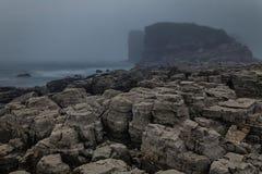 岩石在薄雾掩藏的海岸线和高峭壁,剧烈的风景 免版税库存图片