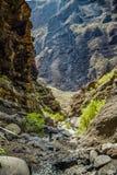 岩石在Masca峡谷,特内里费岛,显示变硬的火山的熔岩流层数和曲拱形成 山沟或barranco主角 库存图片