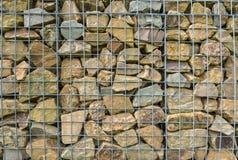 岩石小大块在滤网篱芭后的 图库摄影