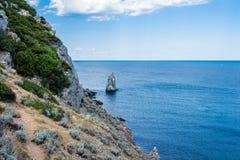 岩石山片断在有蓝天的海在背景 免版税库存图片