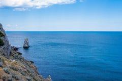 岩石山片断在有蓝天的海在背景 库存照片