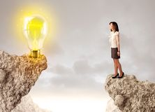 岩石山的女实业家与想法电灯泡 免版税图库摄影