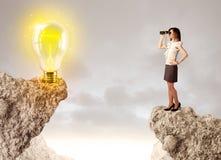 岩石山的女实业家与想法电灯泡 免版税库存图片