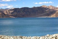 岩石岸和水在湖班公错 库存图片
