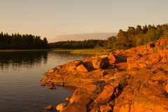 岩石岸在Aland由白夜照亮了 图库摄影