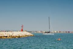 岩石岸,蓝色海,皮船的,有乘客的一条白色游艇,清楚的蓝天一个人 图库摄影