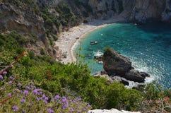 岩石峭壁围拢的美丽的秘密维尔京海滩 开花紫罗兰 corfu希腊海岛 免版税库存图片