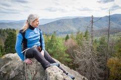岩石峰顶的女性登山人用上升的设备 免版税库存照片