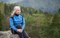 岩石峰顶的女性登山人用上升的设备 图库摄影
