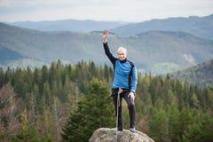 岩石峰顶的女性登山人用上升的设备 免版税图库摄影