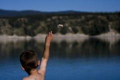 岩石投掷的男孩 免版税图库摄影