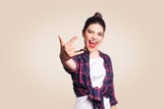 岩石标志 显示与手指的愉快的滑稽的暴牙的兴高采烈的少妇岩石标志 在米黄背景射击的演播室 免版税库存照片
