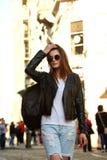 岩石样式的妇女与背包走在城市街道正方形的 库存照片