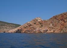 岩石海岸和山向海 库存照片