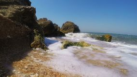 岩石海滨和泡沫似的波浪事件在奔跑 股票视频