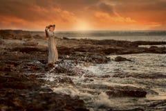 岩石海滨的美女在日出 免版税库存图片