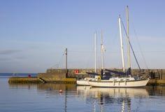 岩石海滩和石被建立的复制品设防在Groomsport海滨村庄在计数下来在北Irel 免版税库存照片