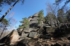 岩石的一张美好的底视图与石头的第一根杆在和有在储备的疆土的一个森林视图下 图库摄影