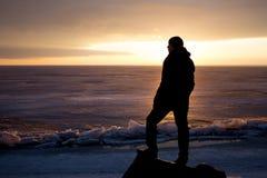 岩石的人在冰的海-剪影 免版税库存图片