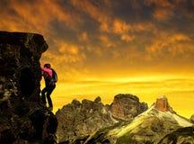 岩石的女孩在日落 免版税库存照片