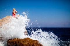 岩石的女孩在海 免版税库存照片
