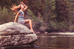 岩石的女孩由湖 免版税图库摄影