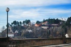 岩石的峭壁的老西班牙传统房子在特鲁埃尔省和一个开花的扁桃附近的 免版税库存图片