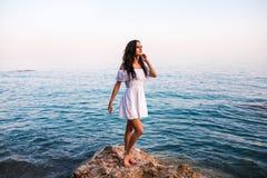 岩石的年轻美女在海 免版税库存照片