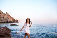岩石的年轻美女在海 免版税库存图片