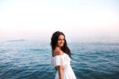 岩石的年轻美女在海 库存照片