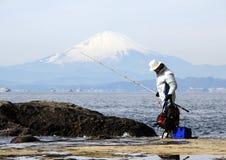 岩石的渔夫在富士山背景的太平洋 免版税库存照片