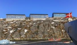 岩石的蓝色因纽特人房子沿有船和小船的海湾 免版税库存图片