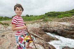 岩石的年轻男孩在海前面 库存照片