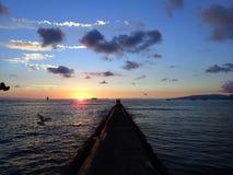 岩石码头导致在太平洋的日落 免版税图库摄影