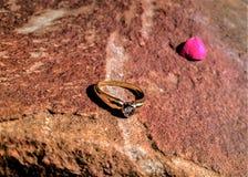 岩石表面上的金结婚戒指 免版税库存图片