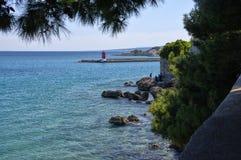 岩石边缘的人们在Krk海岛上的巴斯卡镇2017年4月30日 克罗地亚 免版税图库摄影