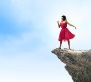 岩石边缘的妇女 免版税库存照片