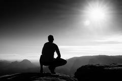 岩石锋利的峰顶的亭亭玉立的游人在岩石帝国公园观看在有薄雾和有雾的早晨谷对太阳 库存照片