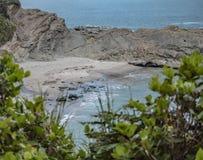 岩石露出阻拦的海滩 免版税库存照片