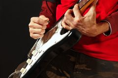 岩石音乐家在黑背景的电吉他上把弦的手指放 免版税库存图片