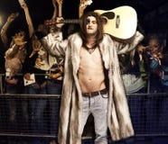 年轻岩石音乐家画象有摆在为激动的观众的吉他的在音乐会 免版税库存照片
