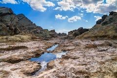 岩石风景在与云彩的天空下 免版税库存照片