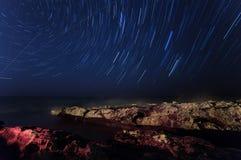 岩石 满天星斗的夜空 海 被突出的海 照相机导致了地球风险长的移动循环s星形线索 免版税图库摄影