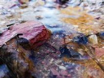 岩石细节在熔化雪水小河的  免版税库存照片
